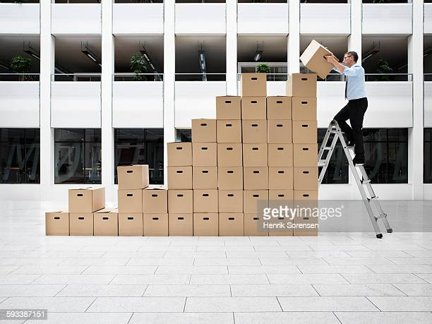 Business man adding box to a stack of boxes