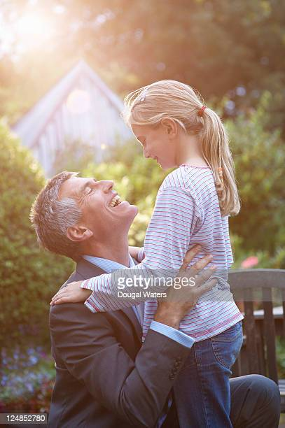 Business man and daughter in garden.