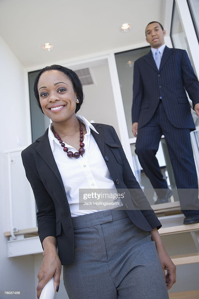 Business man and woman coming down stairs : Stock Photo
