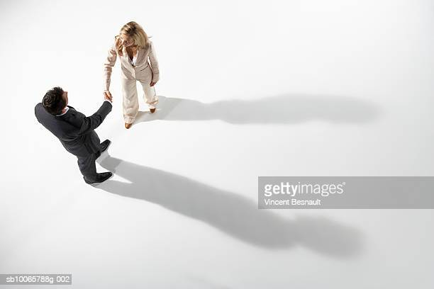 Business man and woman exchanging handshake, shadow showing otherwise