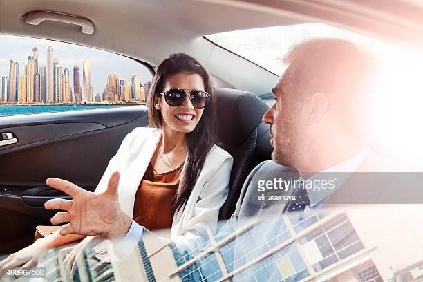 Homme d'affaires et femme dans le siège arrière de voiture de Dubaï