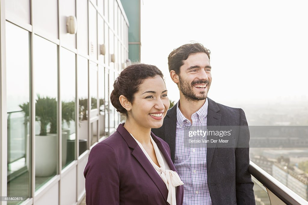 Business man and woman overlooking city. : Stock Photo