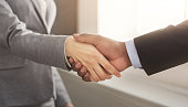 Business handshake closeup. Black man welcoming businesswoman