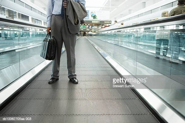 Business man at airport, carrying briefcase and jacket, low section