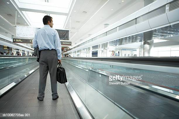 Business man at airport, carrying briefcase, rear view