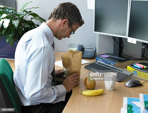 Business man at desk peering into lunch bag
