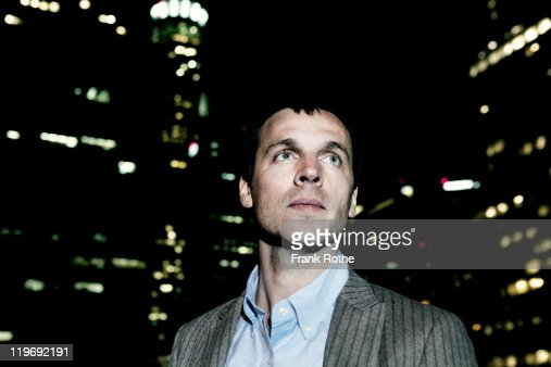 business man at night sourrounded by big city : Stock Photo