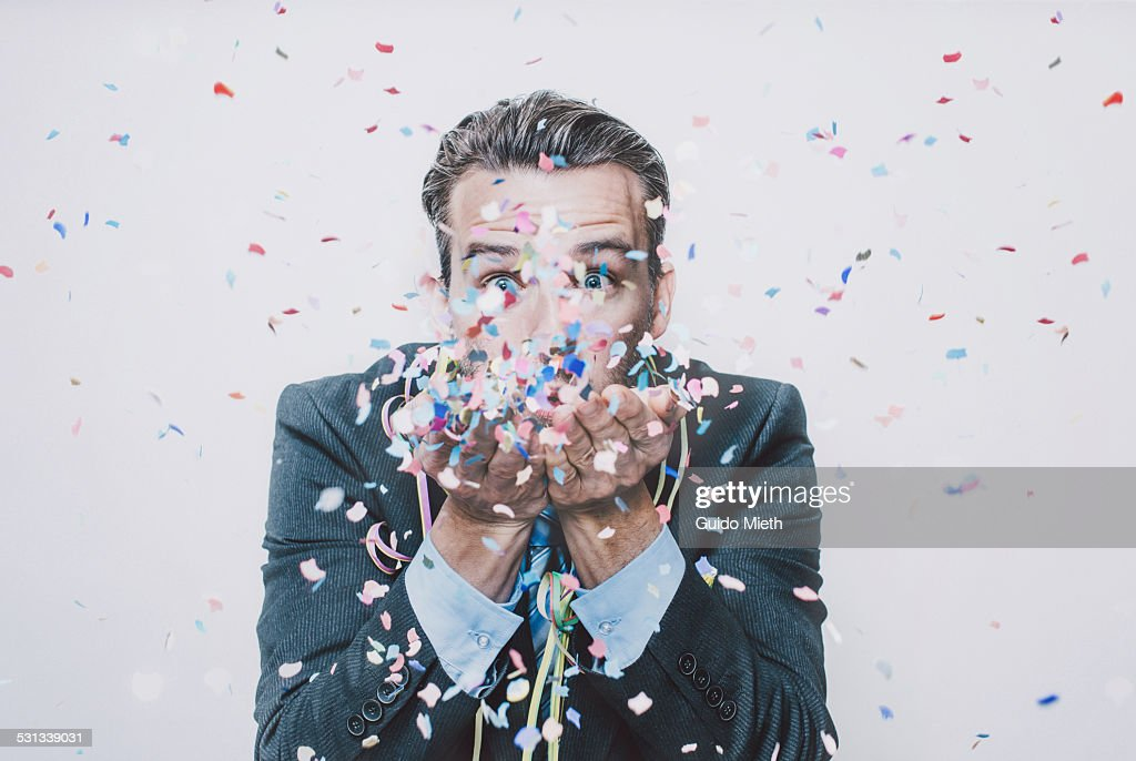 Business man blowing confetti.
