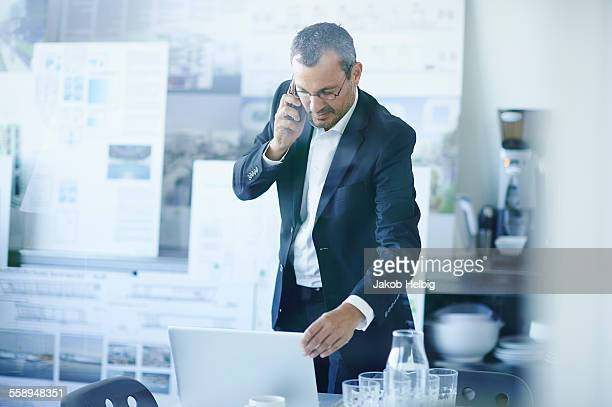 Business man chatting on smartphone whilst using office laptop