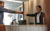 Businessman passes his passport to a smiling receptionist behind the hotel counter. Check-in process in luxurious hotel.