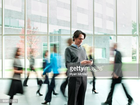 Business man checking phone, crowd moving past : Stock Photo