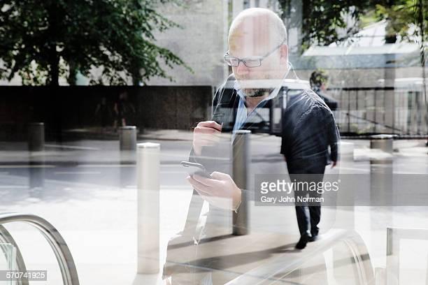 Business man checking phone, shot through window.