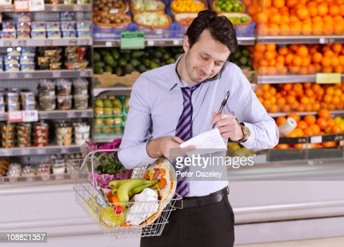 Business man checking shopping list : Stock Photo
