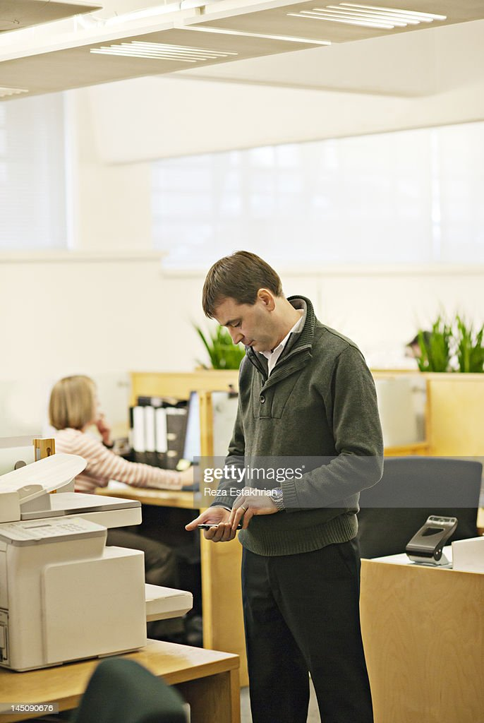 Business man checks cell phone : Stock Photo