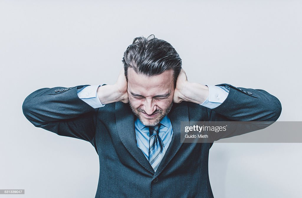 Business man covering his ears.