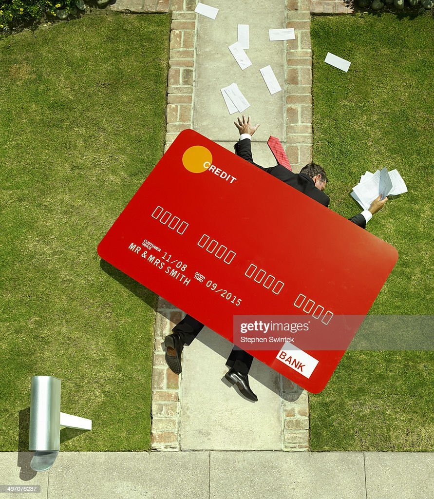 Business man crushed under oversized credt card : Stock Photo