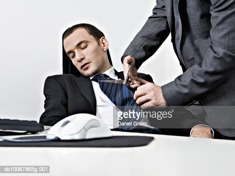 Business man cutting off sleeping colleague's tie in office