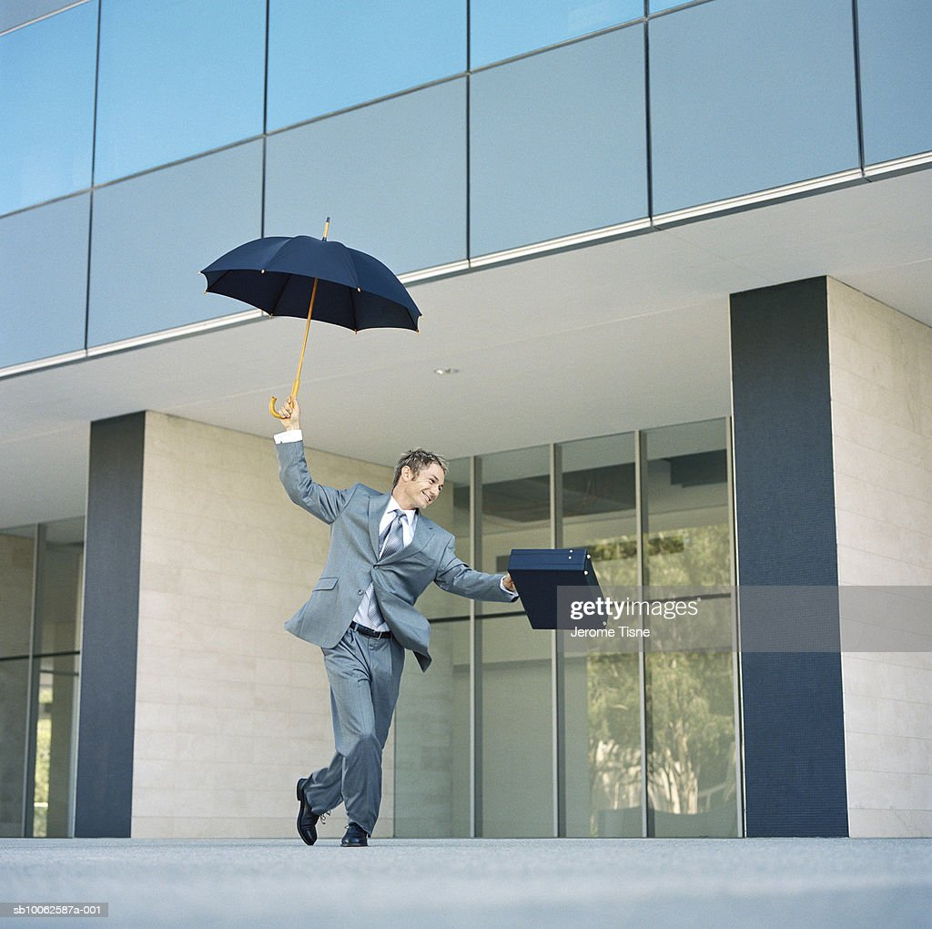 Business man dancing with umbrella and briefcase in front of office building : Stock Photo