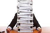 Business man depressed by paperwork (folders)