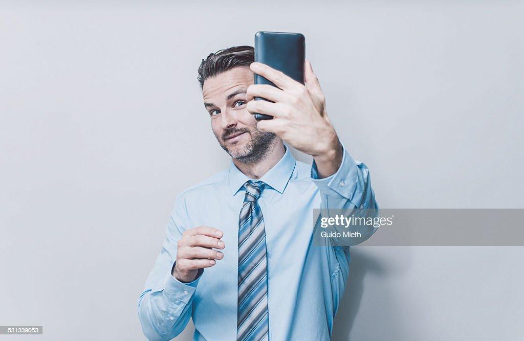 Business man doing selfie.