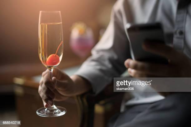 Business man drink champagne and use smart-phone working business wirh darken background