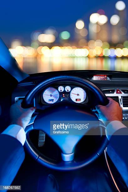 Business man driving car at night