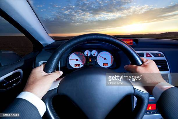 Business man driving car at sunset