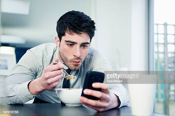 business man eating breakfast with mobile
