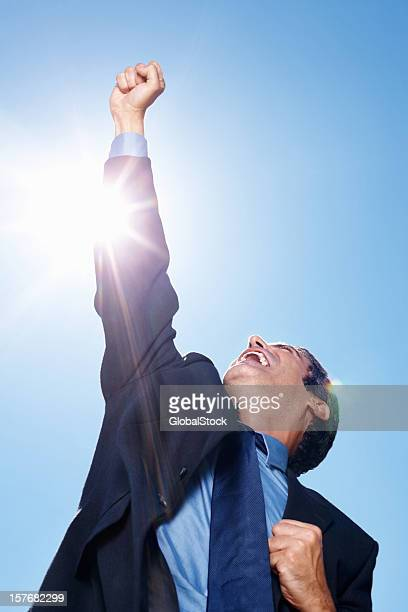 Business man enjoying victory against blue sky