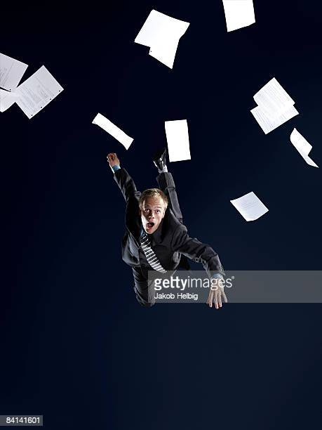 Business man falling, papers flying around in air