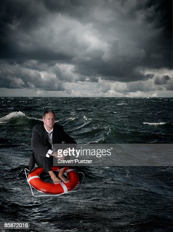 Business man floating on life ring in stormy water