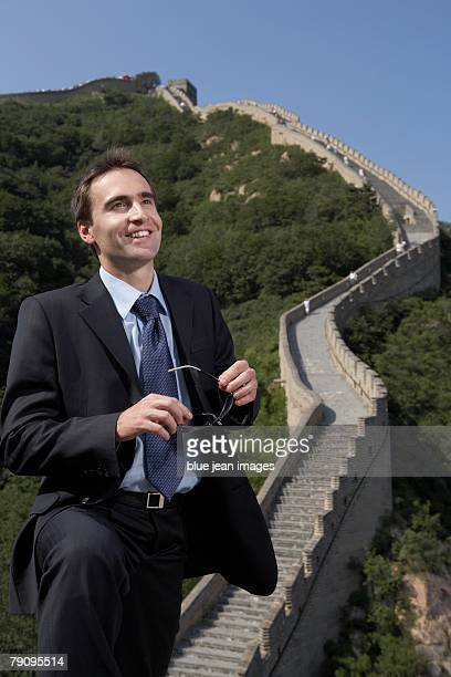 A business man gazing into the distance on the Great Wall.