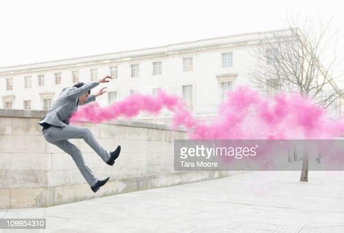 business man getting thrown in air by pink smoke : Stock Photo