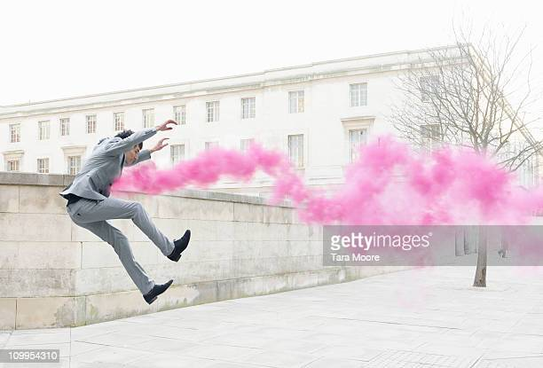 business man getting thrown in air by pink smoke
