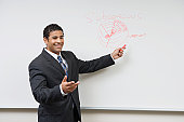 Business man giving presentation standing at whiteboard