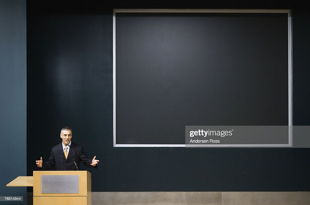 Business man giving speech at podium : Stock Photo
