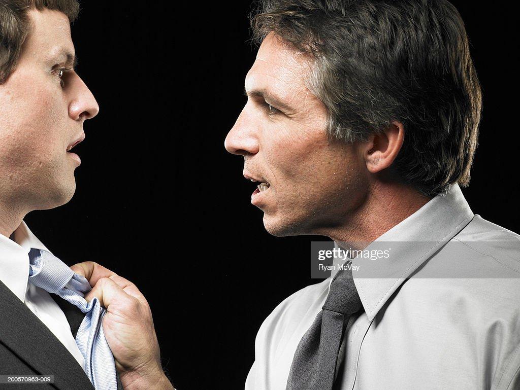 Business man grabbing colleagues shirt, close-up, profile : Stock Photo