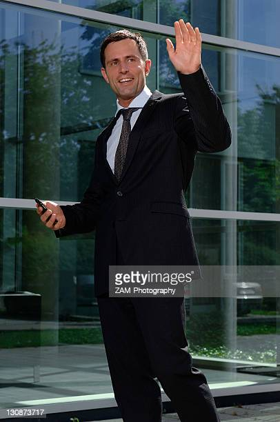 Business man greeting someone outside a bank