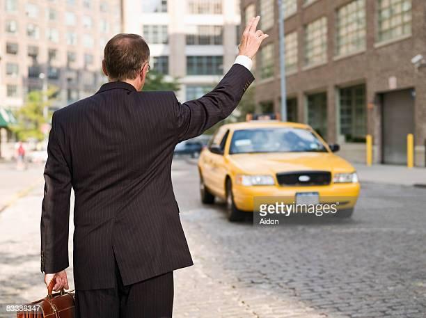 Business man hailing taxi