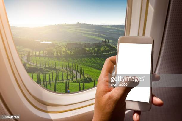 business man hand holding blank screen smart-phone on board of airplane near window seat and wing with Tuscan valley