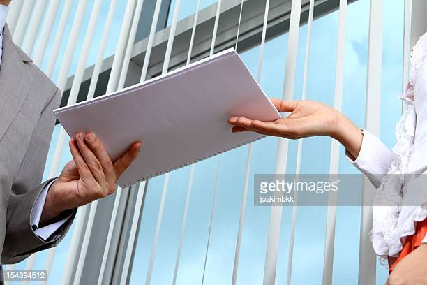 Business man handing documents over to his secretary