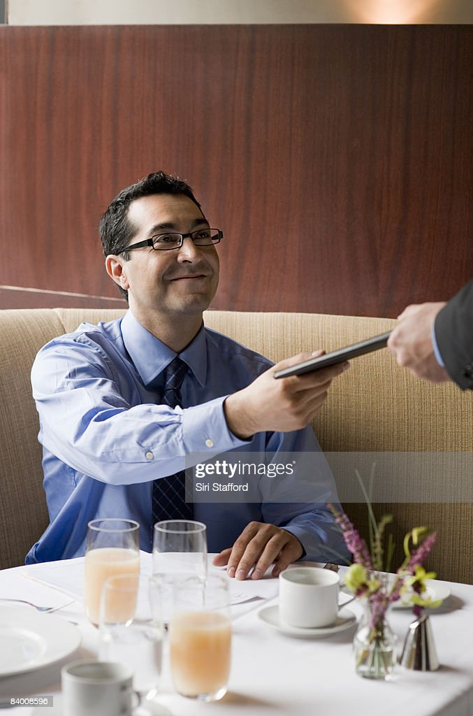 Business man hands check to waiter. : Stock Photo