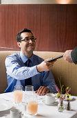Business Mann Hand überprüfen Sie dem Kellner.