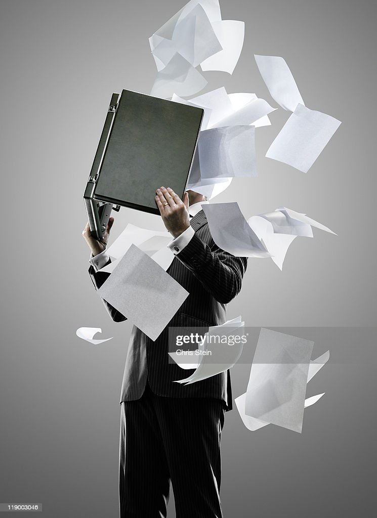 Business man holding a briefcase with flying paper : Stock Photo