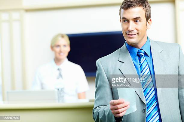 Business man holding a ticket with receptionist in background