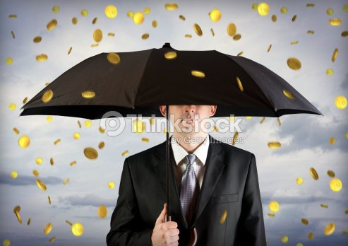 Business man holding an umbrella, money falling from the sky : Stock Photo