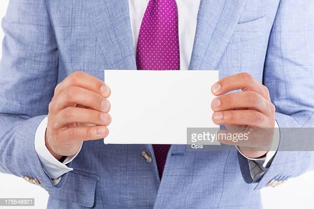 Hombre de negocios sosteniendo una tarjeta en blanco