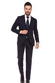 modern young business man holding hand on suit's button is stepping forward on white background