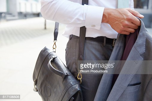 Business man holding his jacket and bag