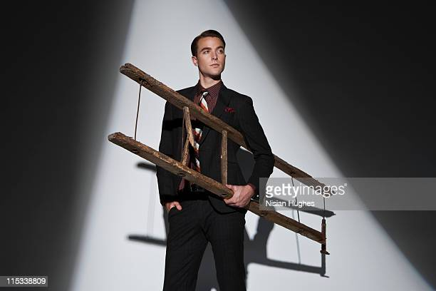 Business man holding ladder